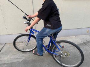 自転車の乗って片手で釣り竿を持っている写真