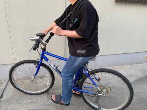 肩に釣り竿を担いで自転車に乗っている写真