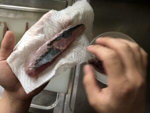魚の水分をキッチンペーパーで取っている写真